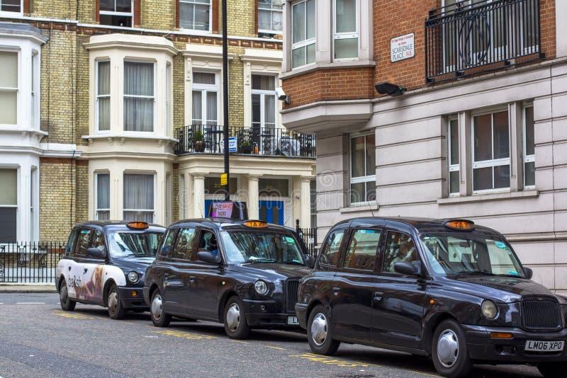Londres, Gran Breta?a 12 de abril de 2019 Calle de Kensington Aparcamiento del taxi El taxi de Londres se considera el mejor taxi fotos de archivo