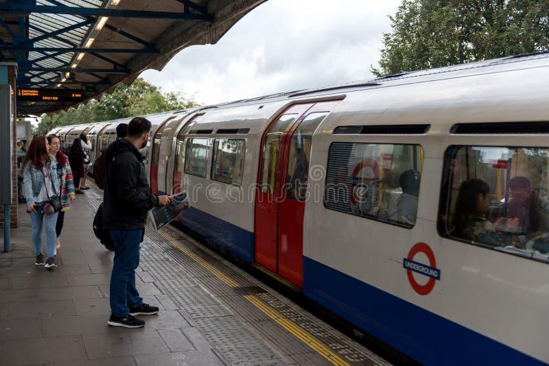 LONDRES, INGLATERRA - 28 DE SETEMBRO DE 2017: Estação subterrânea do metro de Londres com trem e povos imagem de stock royalty free