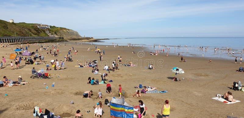 Londres, Inglaterra, Folkestone, kent: 1? de junho de 2019: Os turistas em areias ensolaradas encalham a aprecia??o da luz do sol fotos de stock royalty free