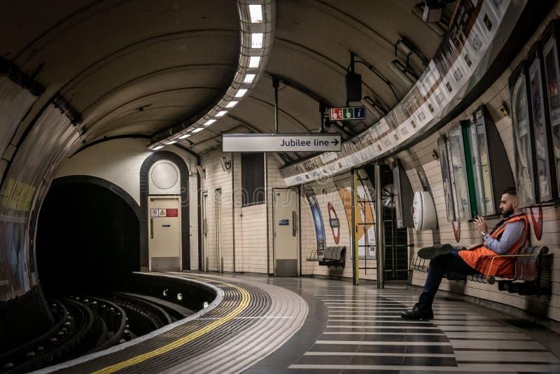 LONDRES, INGLATERRA, O 10 DE DEZEMBRO DE 2018: Povos que esperam o trem na estação de metro de Waterloo completa com sinais e pro fotografia de stock