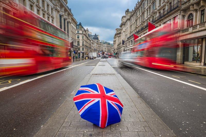 Londres, Inglaterra - paraguas británico en Regent Street ocupado con los autobuses de dos plantas rojos icónicos fotos de archivo libres de regalías