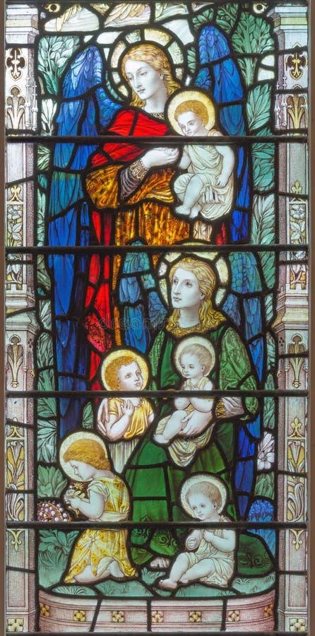 Londres - les anges avec les enfants sur le verre souillé dans la trinité sainte Brompton d'église photographie stock libre de droits