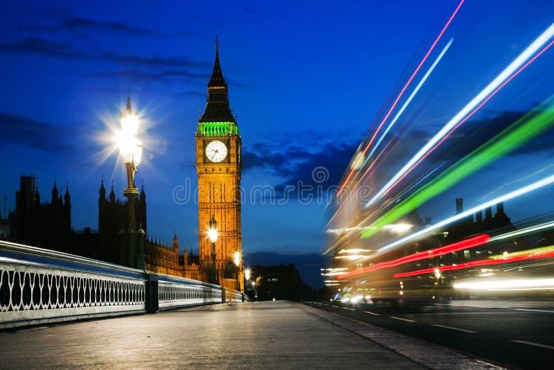 Londres, o Reino Unido. Ônibus vermelho no movimento e Big Ben na noite fotos de stock