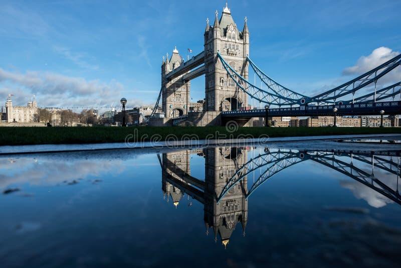 Londres - puente de la torre reflejado en un charco de la lluvia foto de archivo