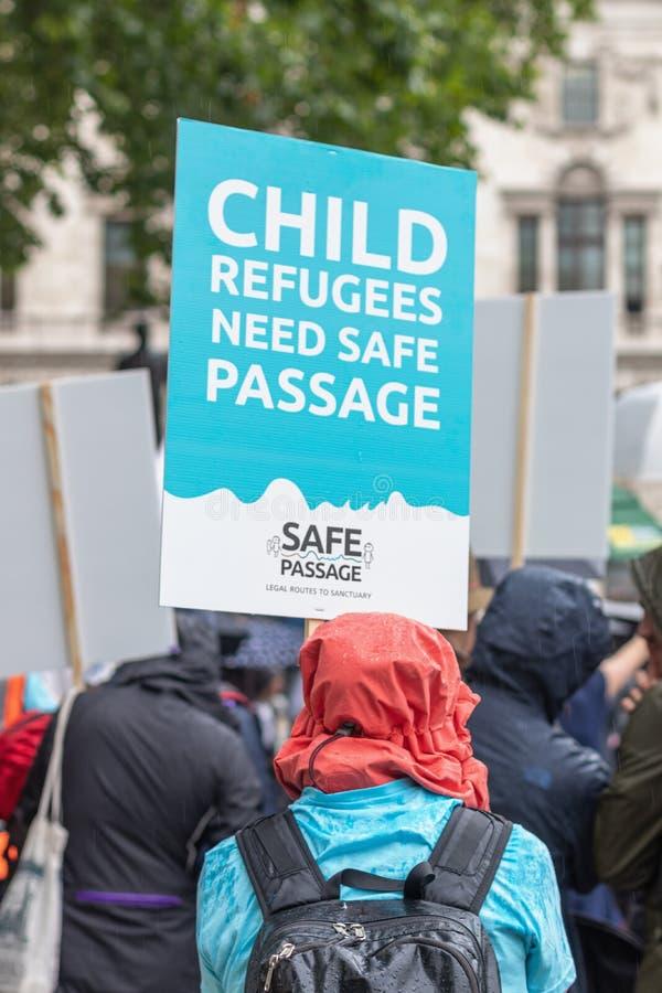 Londres/R-U - 18 juin 2019 - démonstrateur avec un signe invitant le Parlement à donner le passage sûr aux enfants de réfugié photographie stock libre de droits