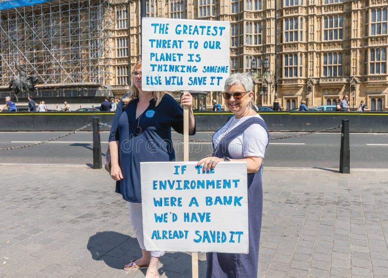 Londres/R-U - 26 juin 2019 - deux femmes tenant des signes en dehors du parlement au sujet du changement climatique photographie stock libre de droits