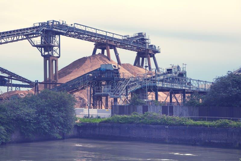 LONDRES, R-U - 4 MAI 2015 : Site industriel chez la Tamise Offre de ciment Récipients contre de lumière de coucher du soleil image libre de droits