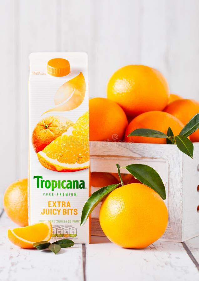 LONDRES, R-U - 31 MARS 2018 : Paquet de jus d'orange tropical frais de Tropicana avec les oranges crues fraîches en bois blanc photos stock