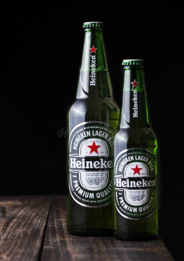 LONDRES, REINO UNIDO - 27 DE ABRIL DE 2018: Botellas de Heineken Lager Beer en fondo de madera oscuro imágenes de archivo libres de regalías