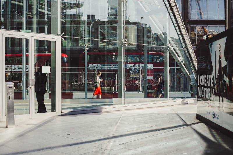 LONDRES, Reino Unido - 14 de abril de 2015: mujer de negocios joven que camina a lo largo del camino con tráfico y de los autobus foto de archivo