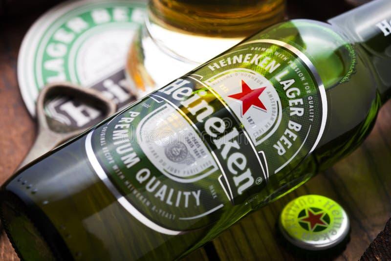 LONDRES, REINO UNIDO - 27 DE ABRIL DE 2018: Vidrio original y botella de cerveza Heineken Lager encima del viejo barril de madera  imagenes de archivo