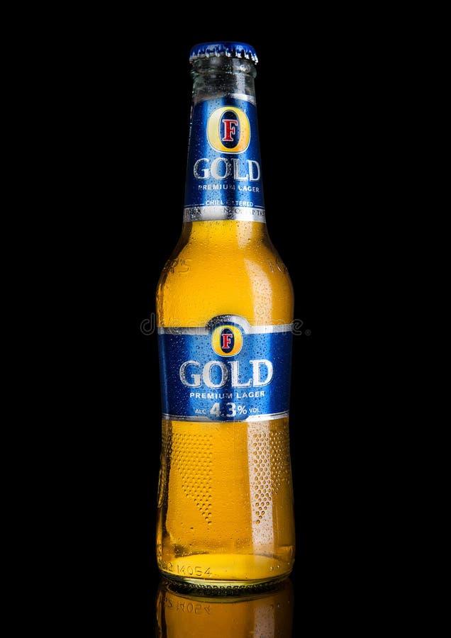 LONDRES, REINO UNIDO - 2 DE ENERO DE 2017: Botella fría del ` s Lager Beer Foster en fondo negro imagen de archivo libre de regalías