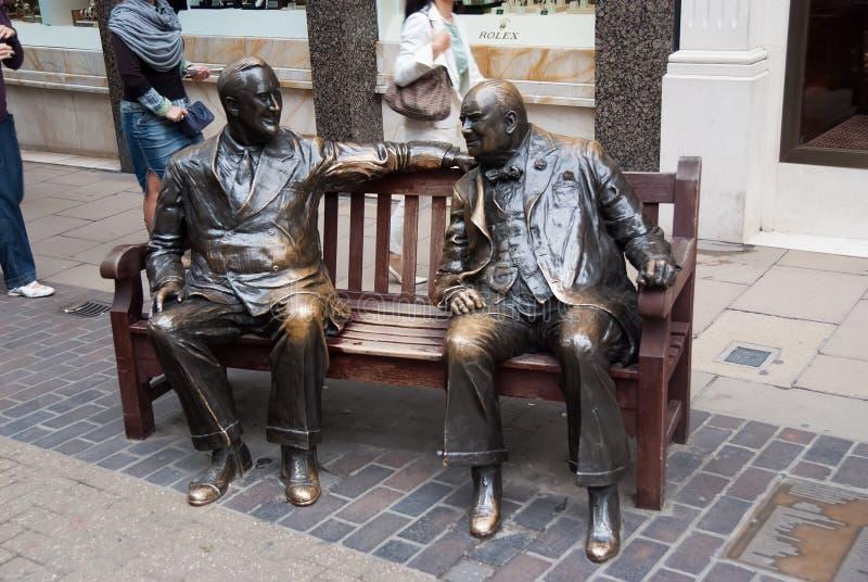 Londres, Reino Unido - 25 de fevereiro de 2010: a escultura dos homens senta-se no banco no bronze Alia a escultura na rua amigos fotos de stock