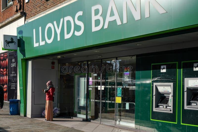 Londres, Reino Unido - 3 de fevereiro de 2019: Mulher desconhecida que verifica seu móbil na frente do ramo do Lloyds Bank em Lew imagem de stock royalty free