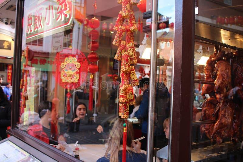 LONDRES, Reino Unido - 16 de fevereiro de 2018: Os povos comemoram o ano novo chinês no restaurante no bairro chinês, Londres foto de stock royalty free