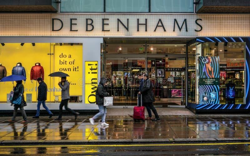 Londres, Reino Unido - 1 de fevereiro de 2019: Pessoas caminham em frente à loja Debenhams da Rua Oxford em um dia chuvoso britân imagens de stock royalty free
