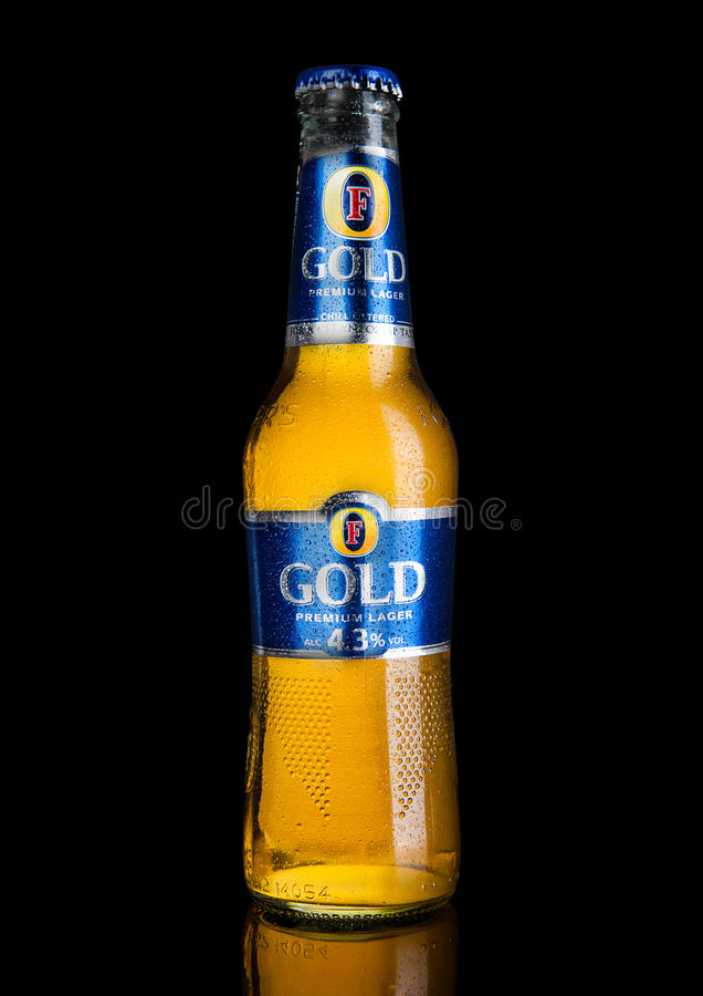 LONDRES, REINO UNIDO - 2 DE JANEIRO DE 2017: Garrafa fria do ` s Lager Beer Foster no fundo preto imagem de stock royalty free