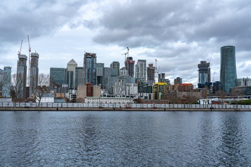 Londres, Reino Unido - 5 de março de 2019: As torres de Canary Wharf vigiam apartamentos, planos e casas do lado do rio ao longo  fotografia de stock