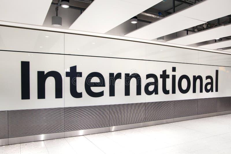 LONDRES, REINO UNIDO - 28 DE MARÇO DE 2015: Sinal internacional das chegadas Interior do terminal de aeroporto 5 de Heathrow Edif fotos de stock royalty free