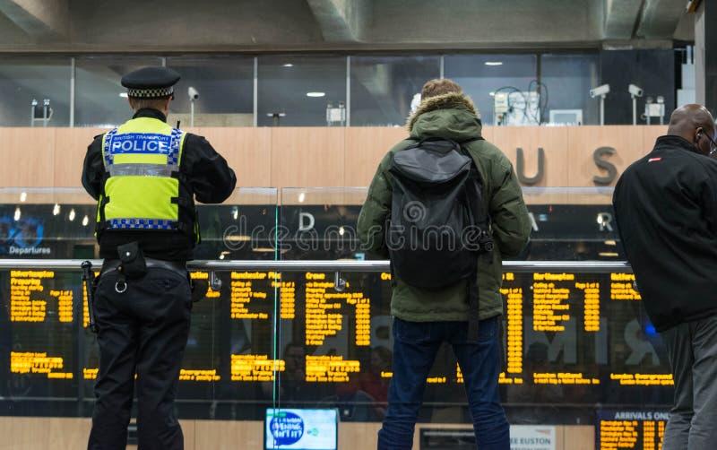 LONDRES, Reino Unido - 17 de octubre de 2017: viajeros de observación del oficial de policía del transporte de británicos que mir imagenes de archivo