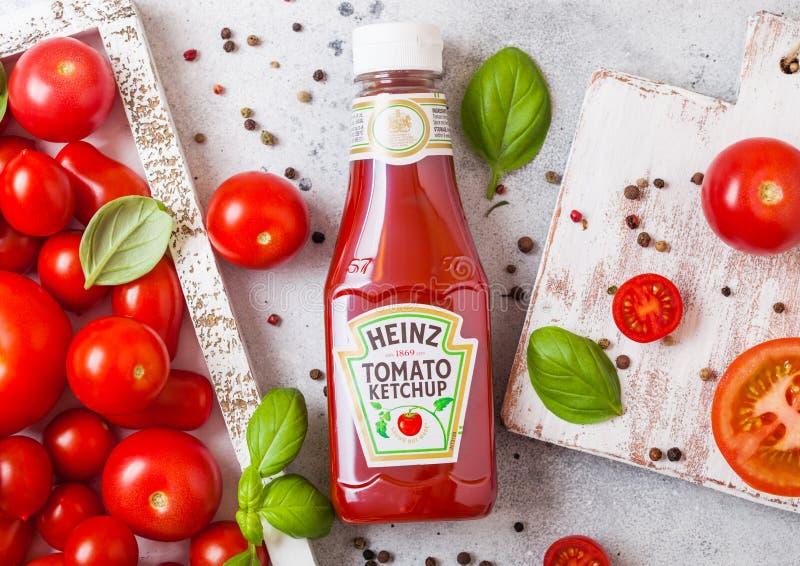LONDRES, REINO UNIDO - 13 DE SETEMBRO DE 2018: Ketchup de Heinz com os tomates crus frescos na caixa no fundo de pedra da cozinha foto de stock royalty free