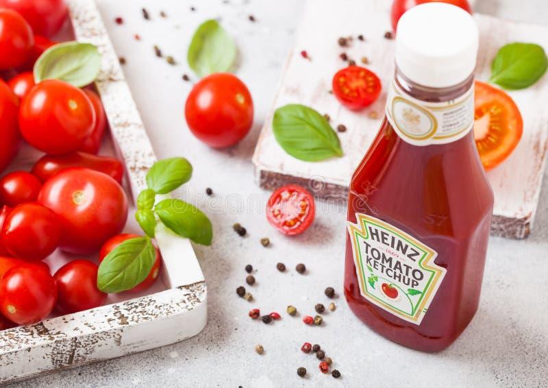 LONDRES, REINO UNIDO - 13 DE SETEMBRO DE 2018: Ketchup de Heinz com os tomates crus frescos na caixa no fundo de pedra da cozinha fotografia de stock royalty free