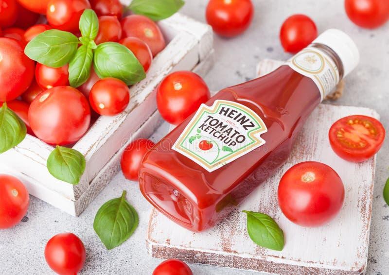 LONDRES, REINO UNIDO - 13 DE SETEMBRO DE 2018: Ketchup de Heinz com os tomates crus frescos na caixa na placa de madeira foto de stock