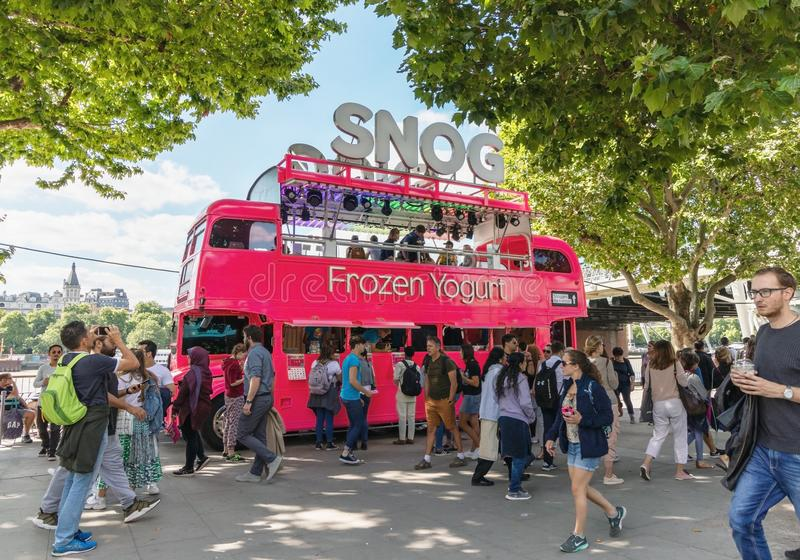 Londres/Reino Unido, el 15 de julio de 2019 - Snog al vendedor del yogurt congelado actúa desde un autobús rosado en paseo del Qu imágenes de archivo libres de regalías