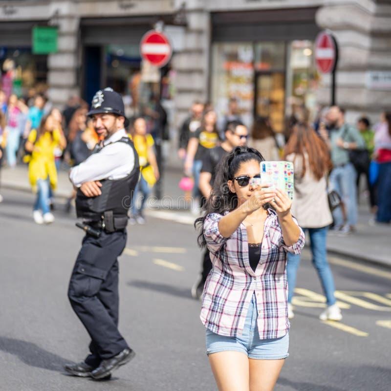 Londres, Reino Unido, el 14 de julio de 2019 Una muchacha en Londres toma un selfie delante de la policía Foco suave fotografía de archivo