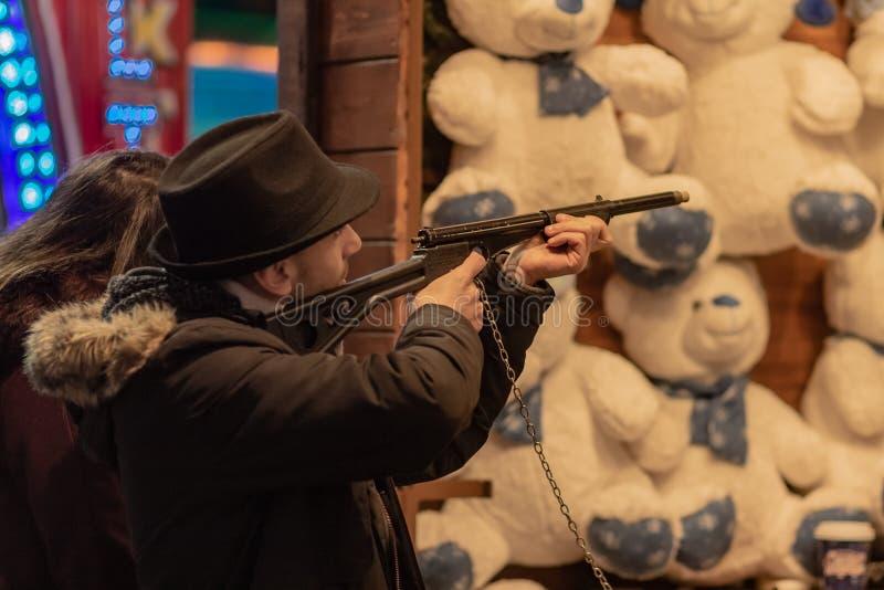 Londres, Reino Unido - 17, em dezembro de 2018: Parque de diversões na noite - homem com o urso do tiro da arma fotos de stock