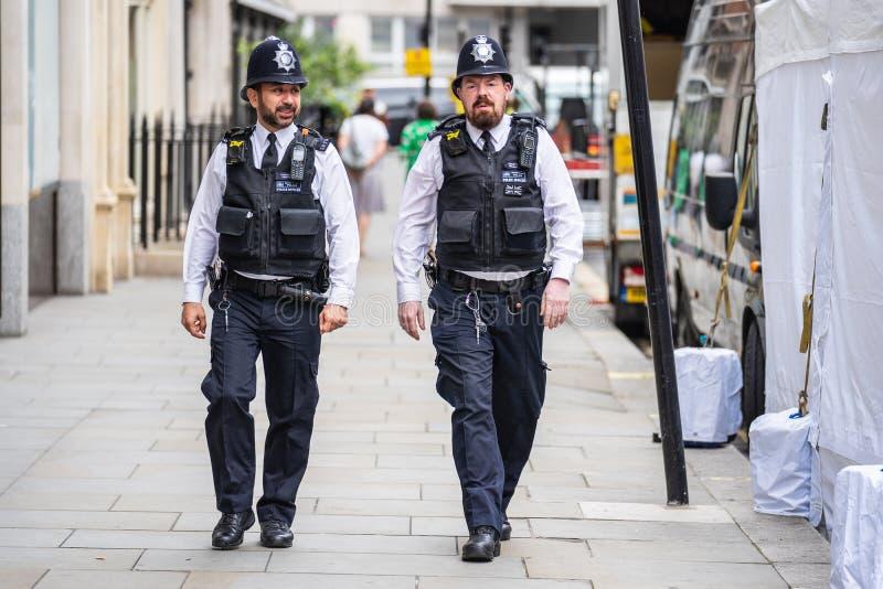 Londres, Reino Unido, em julho de 2019 Dois agentes da polícia britânicos que patrulham as ruas de vestes vestindo da facada de I imagens de stock