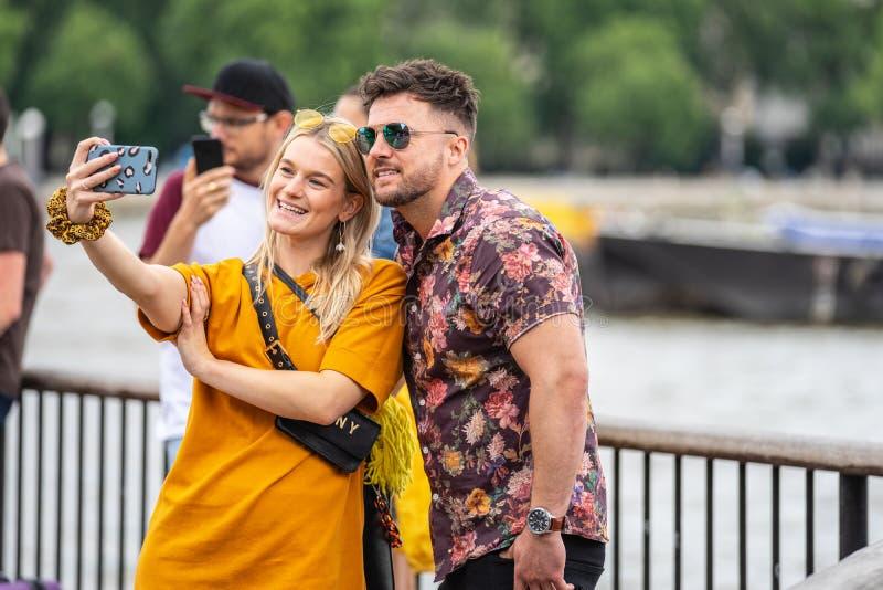Londres, Reino Unido, em julho de 2019 Retrato ascendente próximo dos pares atrativos felizes que tomam o selfie em Londres foto de stock