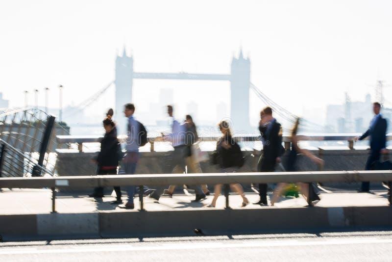 Londres, Reino Unido Imagem borrada dos trabalhadores de escritório que cruzam a ponte de Londres no amanhecer na maneira à cidad imagens de stock