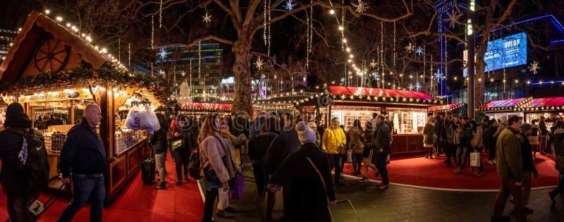 LONDYN, ANGLIA, GRUDZIEŃ 10th, 2018: Ludzie ma zabawę w miło iluminującym boże narodzenie jarmarku podczas gdy chodzący wokoło, r obraz stock