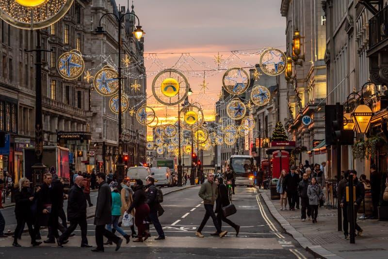 LONDYN, ANGLIA, GRUDZIEŃ 10th, 2018: Udziały ludzie krzyżuje ulicę z samochodami i dwoistego decker autobusem przy światła ruchu zdjęcie royalty free