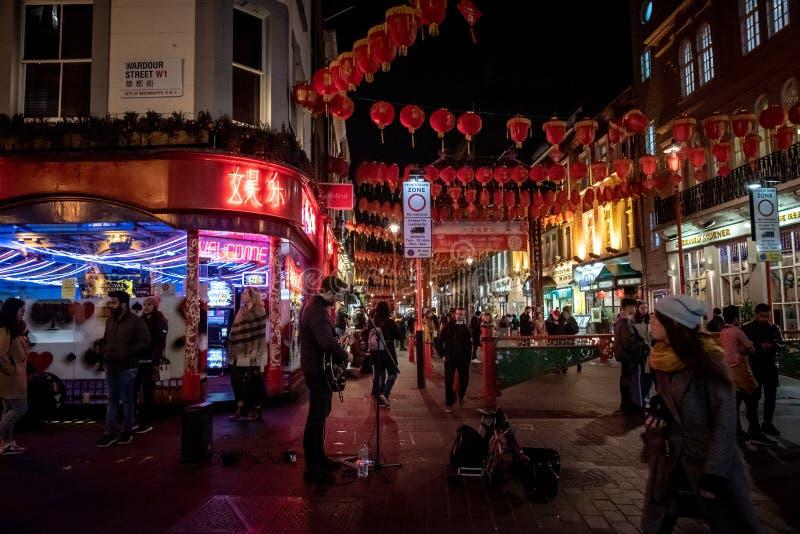 LONDYN, ANGLIA, GRUDZIEŃ 10th, 2018: uliczny muzyk bawić się gitarę pod neonowymi światłami w Chinatown, dekorującym chińczykiem obraz stock