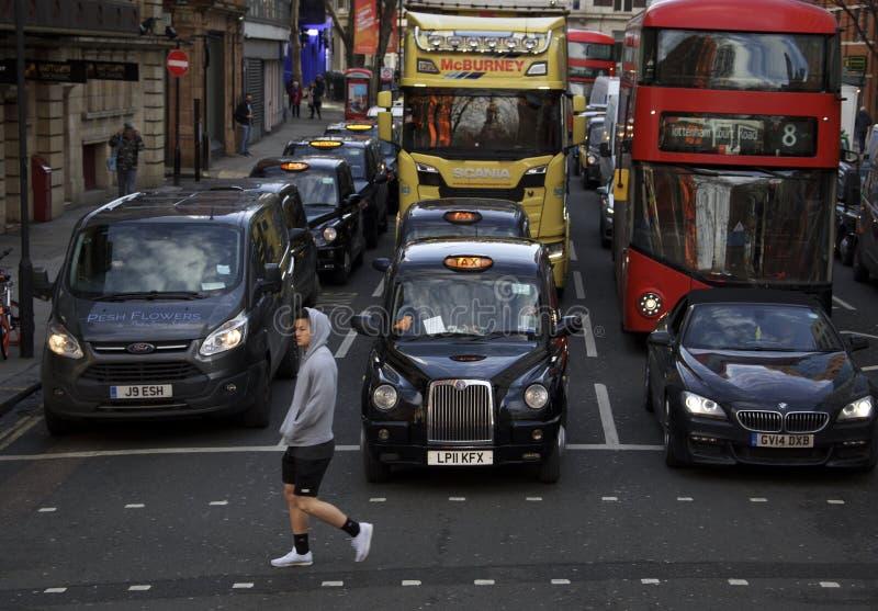 Londyn, Anglia: 8th Marzec 2018: Osoby odprowadzenie przed czarną taksówką i innymi samochodami zdjęcia royalty free