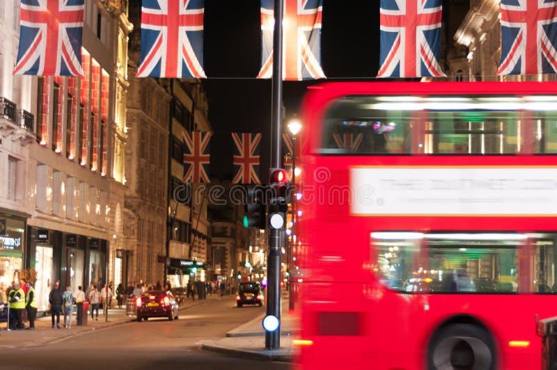 Londyn flagi i London autobus nocą fotografia royalty free