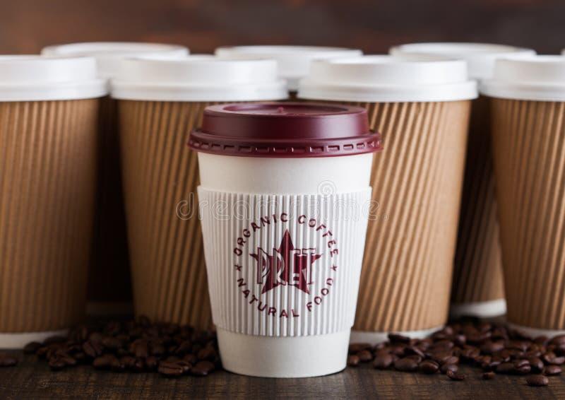 LONDYN, UK - CZERWIEC 05, 2019: Pret żłób Kawowa Papierowa filiżanka dla bierze daleko od z kawowymi fasolami na drewnianym tle z zdjęcie stock