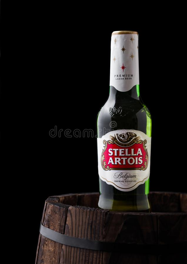 LONDYN, UK - CZERWIEC 06, 2018: Zimna szklana butelka Stella Artois piwo na starej drewnianej baryłce fotografia royalty free