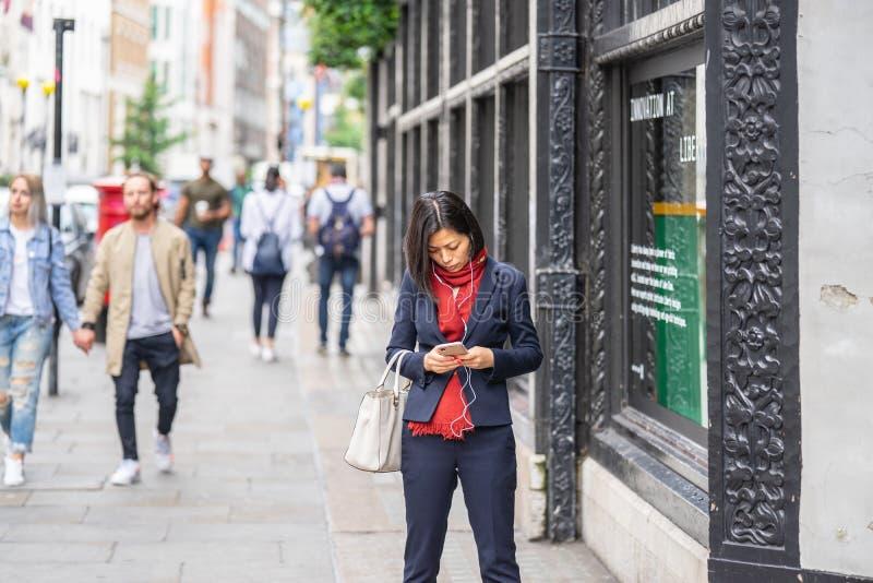 Londyn, UK, Lipiec 14, 2019 Atrakcyjna Azjatycka biznesowa kobieta używa smartphone dojeżdżającego w Londyn zdjęcie royalty free