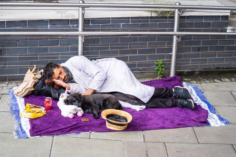 Londyn, UK, Lipiec, 2019 Biedny bezdomny mężczyzny lub uchodźcy dosypianie na miastowej ulicie w mieście, ogólnospołeczny dokumen fotografia stock