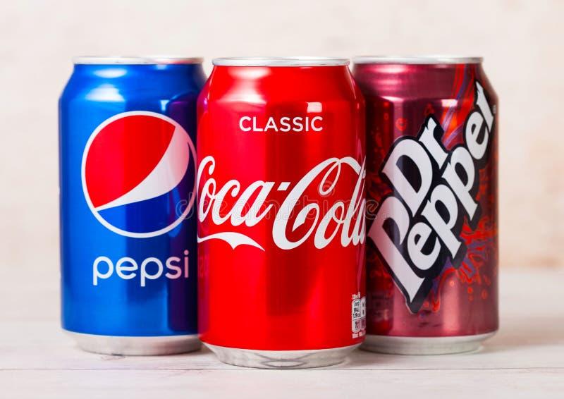 LONDYN, UK - SIERPIEŃ 03, 2018: Aluminiowe puszki koka-kola, Pepsi i Dr Pieprzowy miękki napój na drewnianym tle amerykanin fotografia stock