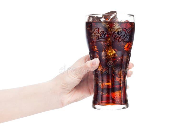 LONDYN, UK - STYCZEŃ 20, 2018: Żeńska ręka trzyma szkło koka-kola napój na bielu Napój produkuje i fabrykuje obrazy royalty free