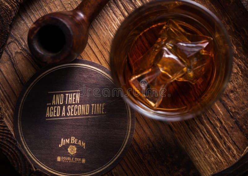 LONDYN, UK - WRZESIEŃ 04, 2018: Szkło Jim promienia bourbonu whisky z oryginalnym kabotażowem i rocznika dymienia drymbą na drewn obrazy royalty free