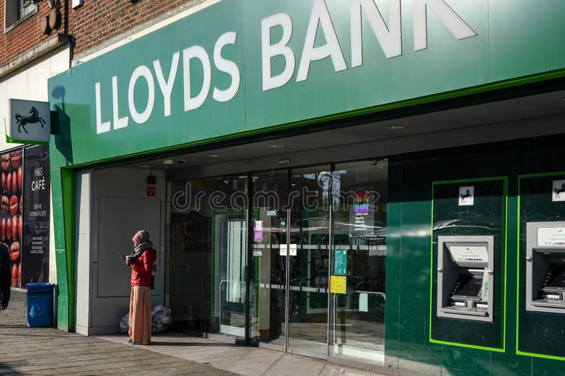 Londyn Zjednoczone Królestwo, Luty, - 03, 2019: Niewiadoma kobieta sprawdza jej wiszącą ozdobę przed lloyds bank gałąź przy Lewis obraz royalty free