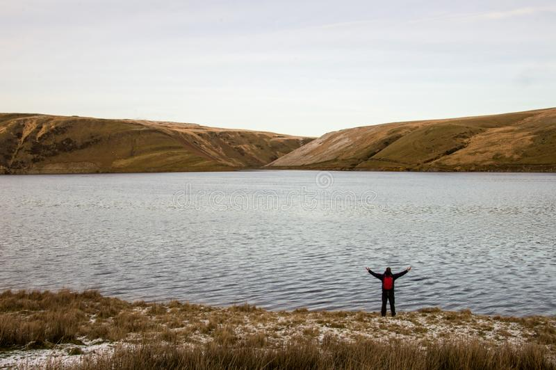 A lone backpacker with arms outstretched standing on the edge of a reservoir looking out on bleak moorland in winter. Elan Valley, royalty free stock image