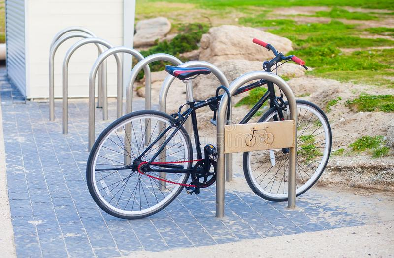 Public bike parking with sole bicycle. Lone bicycle left parked at a public bike parking place royalty free stock images