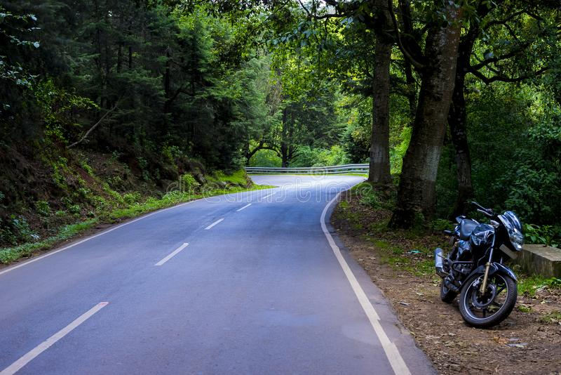 A lone bike in a forest road near Ooty, India royalty free stock image