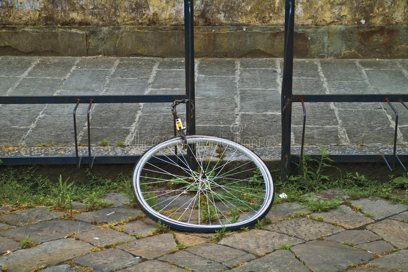 Lone Bike Tire/ Stolen Bike. Bike tire chained to rack after bike is stolen royalty free stock image